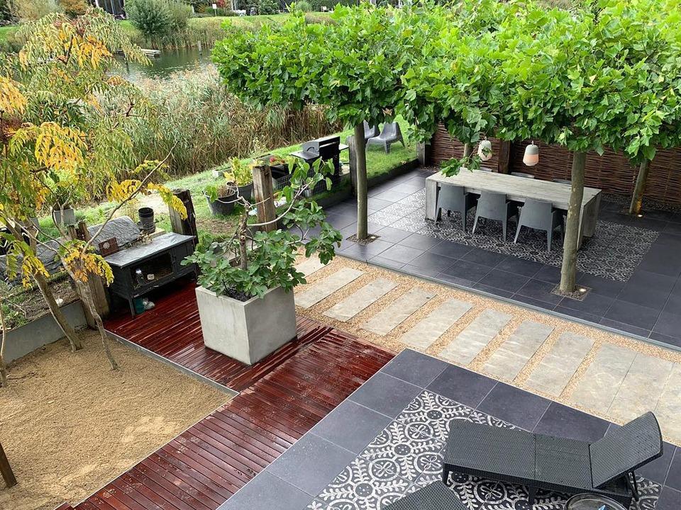 Voorbeeld van een aangelegde tuin met bestrating, vlonders, bomen, verlichting, decoratieve elementen